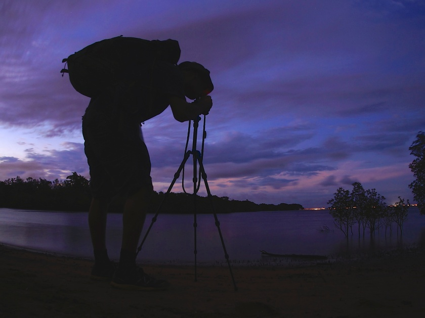 photographer on creek bank at night